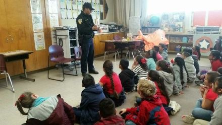 An officer speaks to children at a school event